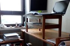 Mittatilaustyönä valmistettu ergonomiakoroke, joka muuntaa tavallisen kirjoituspöydän seisomatyöpisteeksi. Korokkeen välitaso tuo kokonaisuuteen lisää laskutilaa.